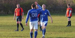 A controversial figure returns. Ex-coach, Neil Richardson, celebrates his goal with current coach, Mickey Pearson.