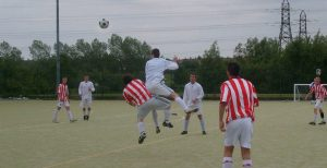 Wooton leaps and uses the full force of his oval head to clear the ball.
